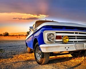 Auto na pláži při západu slunce